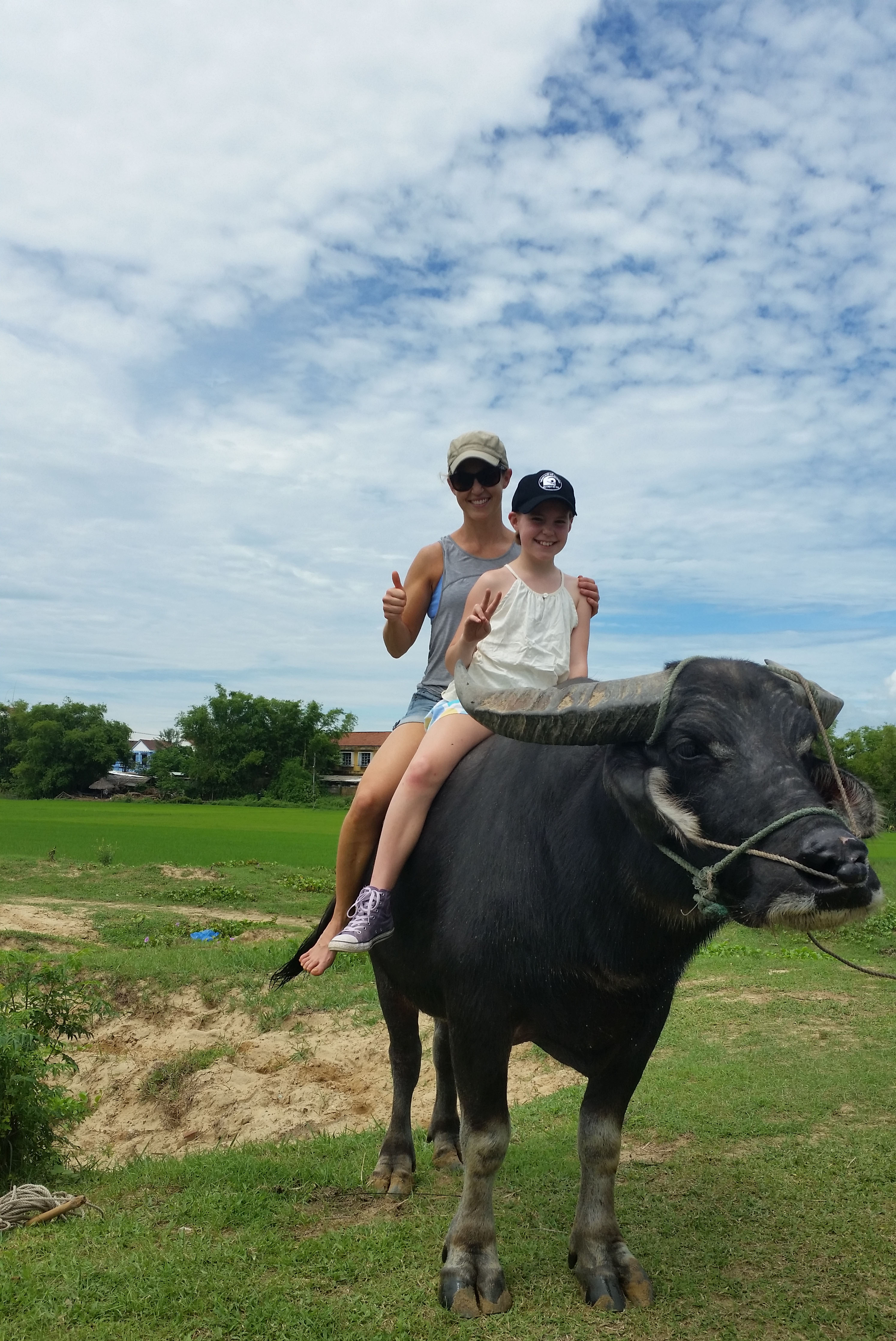 Mother and daughter riding at the back of wild buffalo during the Goddess outdoor fitness Vietnam Trip